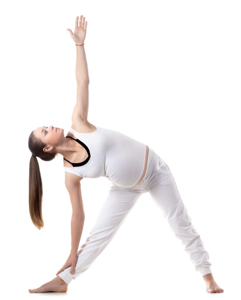 Ung, gravid kvinne som gjør yoga