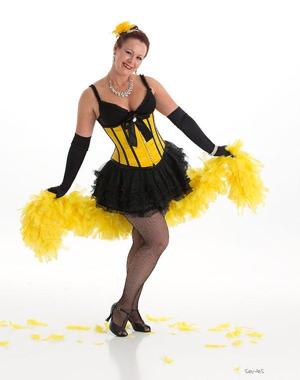 Linn i gult burlesque kostyme med fjærboa
