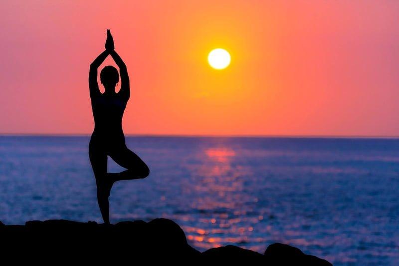 Siluett av kvinne i stående yogastilling i solnedgang ved havet.