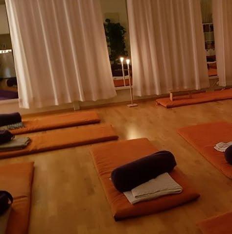 Yogarommet med yogamatter, pledd og bolstere.