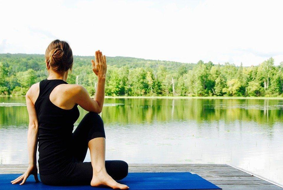 Kvinne i sittende yogastilling ser utover et stille vann.