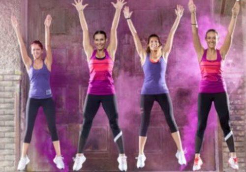 Glade treningsdamer hopper med armene opp