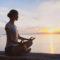 Ung kvinne mediterer ved stille vann i solnedgang
