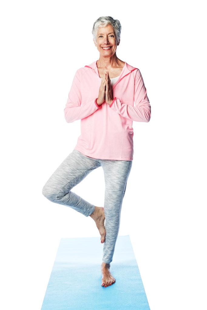 Glad, eldre dame i stående yogastilling på yogakurs.