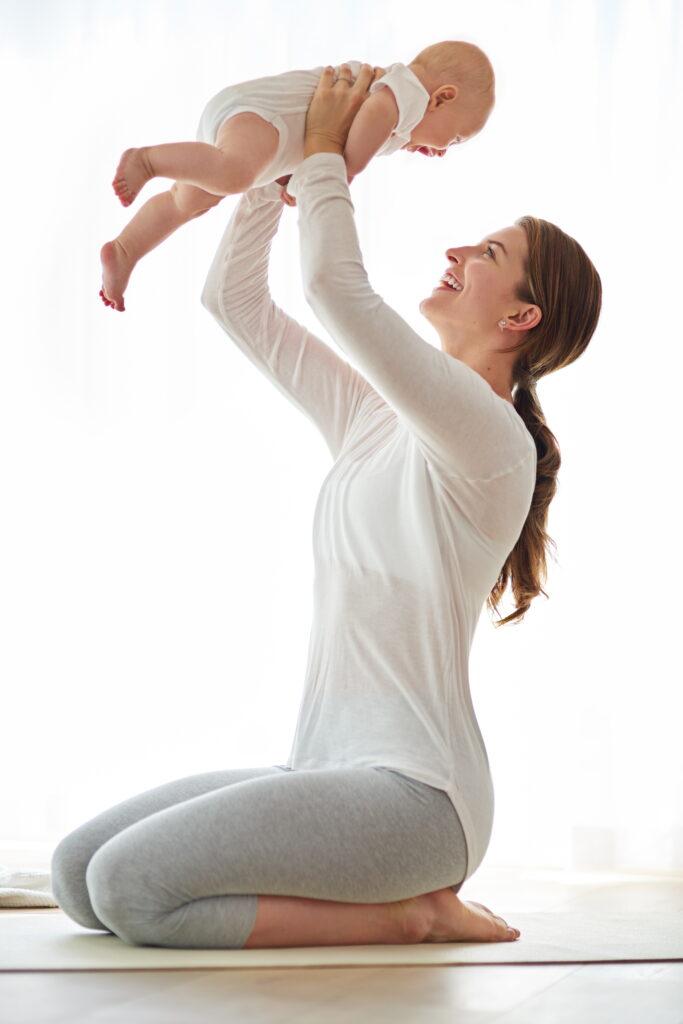 Mamma som løfter babyen sin opp over hodet på Mamma & Baby yogakurs.